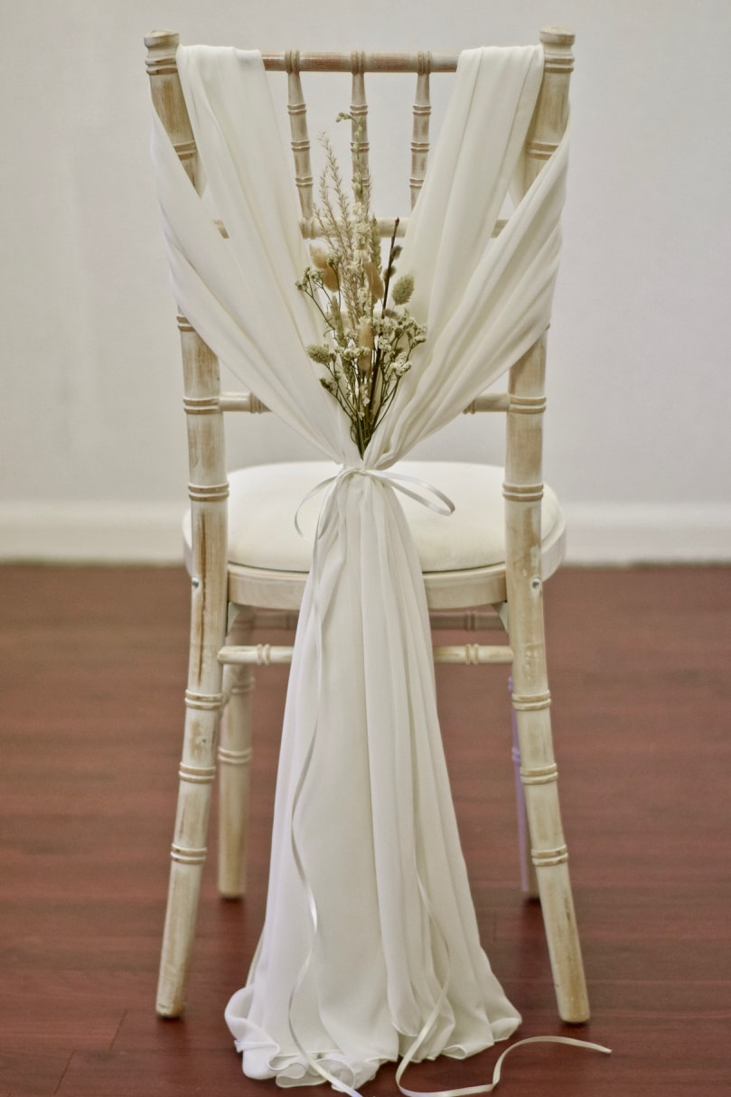 Ivory Chiffon Heart Drape with Dried Floral Arrangement on Chiavari Chair