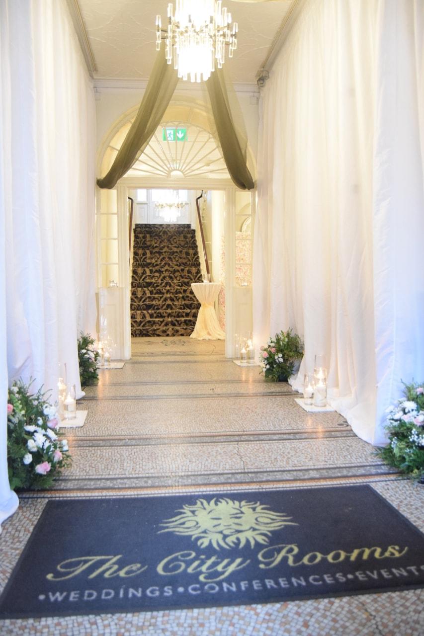 White Pleated Drape Hallway Decoration with Cylinder Vase Decoration and Fresh Floral Arrangements